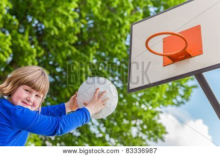 Schoolgirl aiming ball at board with basket