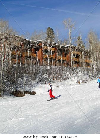 Skiers Slide Past Expensive Townhouses