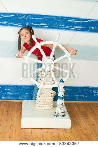 Girl In A Red T-shirt Against A Ship Steering Wheel