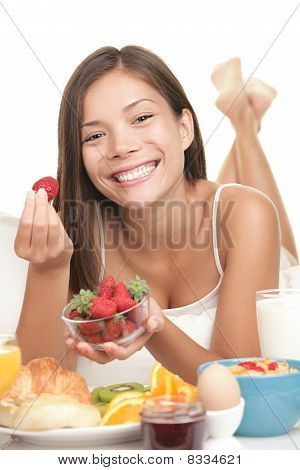 Young Woman Eating Fruits At Breakfast