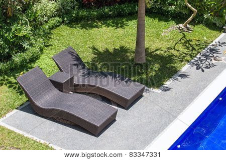 Two Beach Chairs Next To A Swimming Pool In A Tropical Garden. Top View