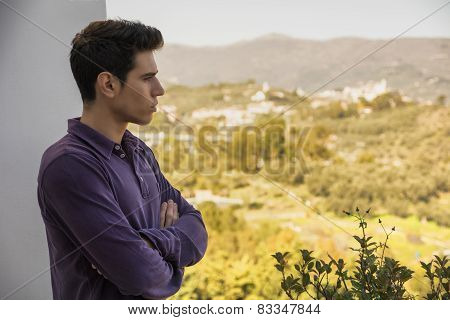 Young Man Standing Looking Over A Rural Landscape