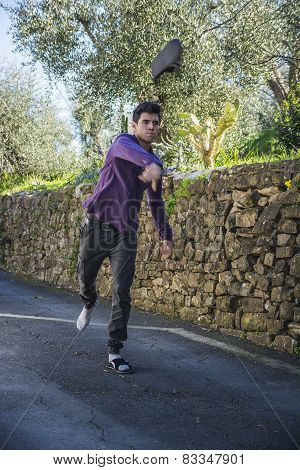 Angry Young Man Tossing His Shoe Through The Air