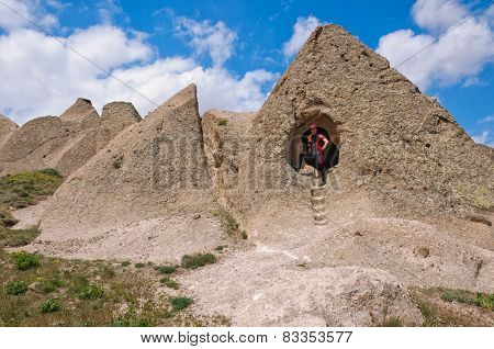 Young Man Stands At The Entrance To A Cave, Cappadocia, Turkey