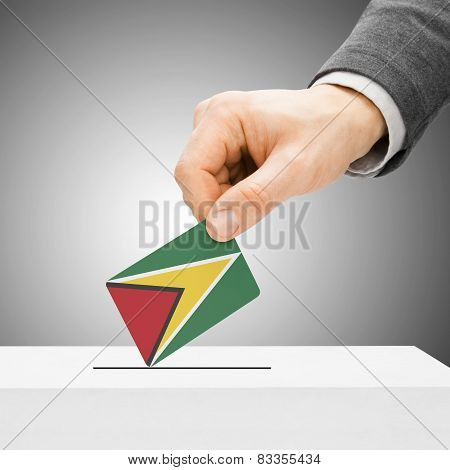 Voting Concept - Male Inserting Flag Into Ballot Box - Guyana