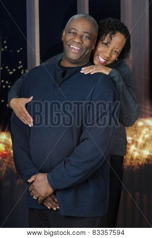 A happy and attractive, mature African American couple before nighttime windows and white Christmas lights.