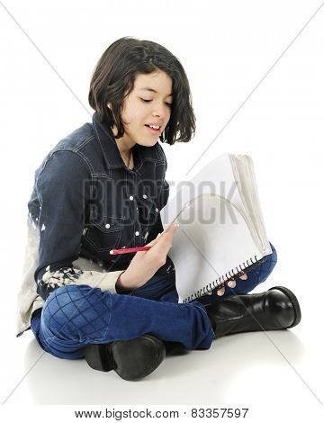 An attractive young teen sitting on the floor checking the work in her note pad.  On a white background.