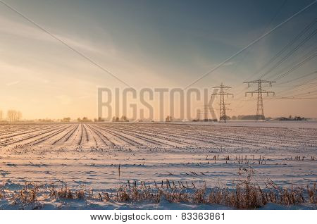 High Voltage Lines And Pylons In A Snowy Stubble Field
