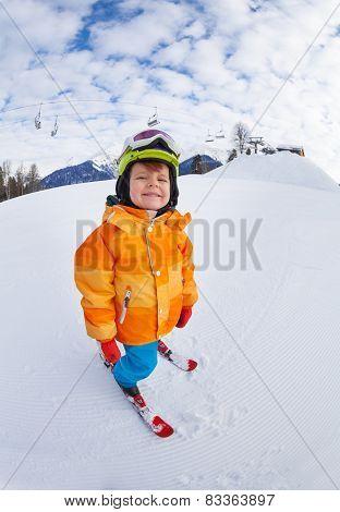 Cheerful boy wearing ski mask and helmet skiing