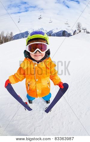 Smiling boy wearing mask holds ski in mountains