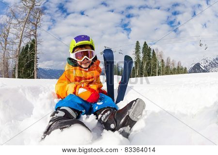 Sitting on snow boy in ski mask and helmet
