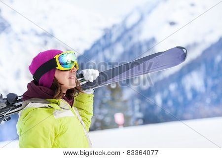 Girl in mask stands and holds ski during day