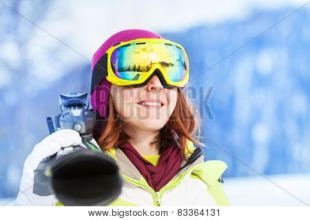 Portrait of happy woman in mask holding ski