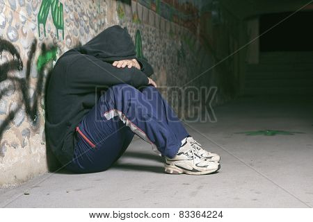 Young man abandoned lost in depression sitting on ground street