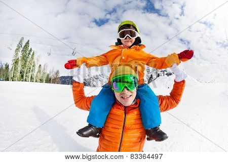 Father and son sitting on shoulders, snow day