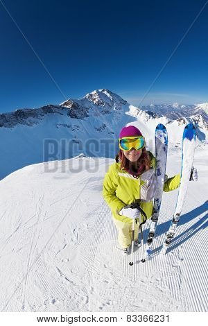 Smiling woman in mask standing and holding ski