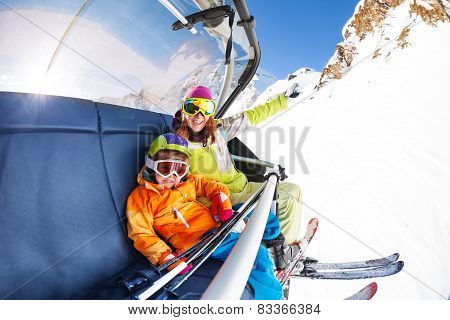 Mom with boy on ski lift ropeway chair