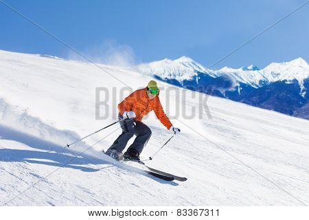 Young man in ski mask sliding fast while skiing