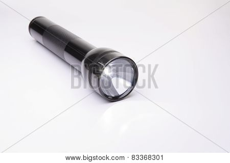 A black flashlight over a gray background on the floor