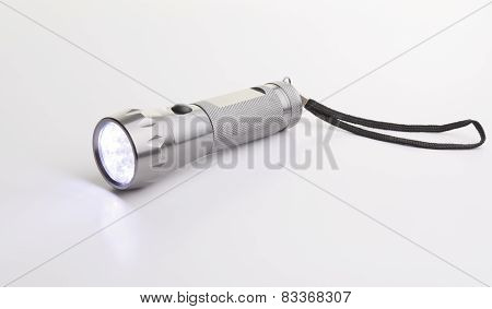 A gray flashlight over a gray background on the floor