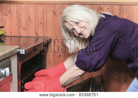 senior woman baking cookies on the stove