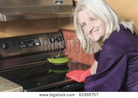 senior woman baking cookies on the stove