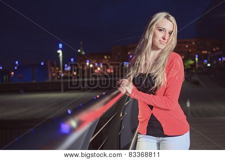 A woman posing on the night life of a city