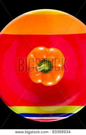 Orange Bell Pepper Sitting On A Colorful Dish
