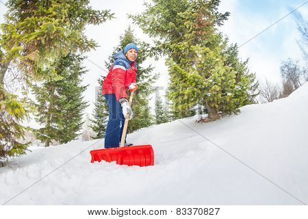 Arabian boy working with shovel and cleaning snow