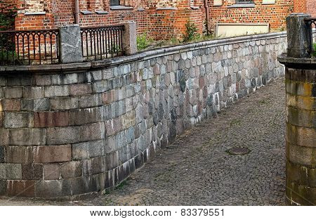 Small Alley Between A Brick Wall