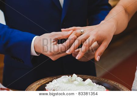 Groom wearing the Diamond ring to bride hand in wedding ceremony. Wedding rings exchange