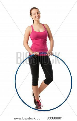 Young woman standing with hula hoop down