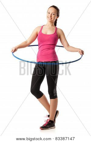 Young woman standing with hula hoop round her waist