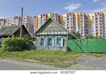 Cottage On The Background Of High-rise Buildings