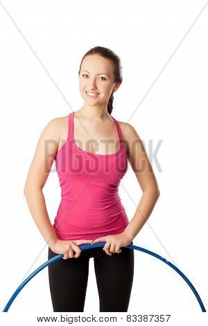 Young woman standing with hula hoop down. Half- length view