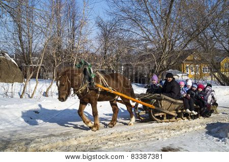 Mstera,Russia-February 21,2015: Children ride on sled with horse at day of the Shrovetide