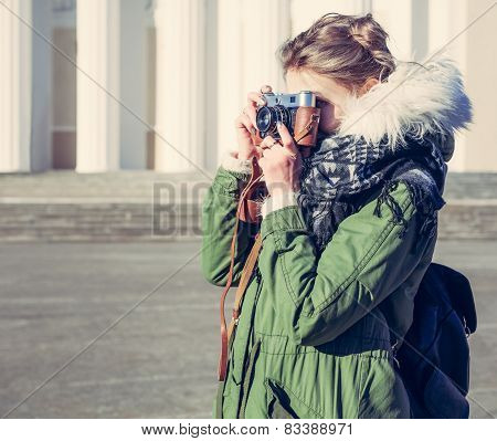 The girl in the green jacket photographs vintage camera outdoors on a sunny spring day. Close up