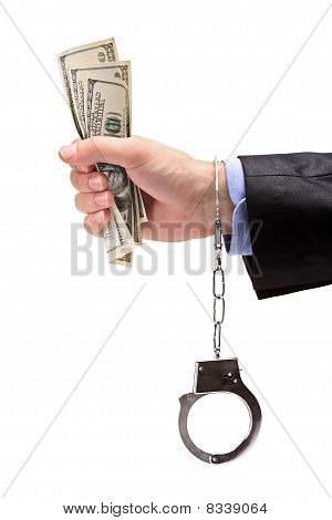 Hand with handcuffs holding US dollars