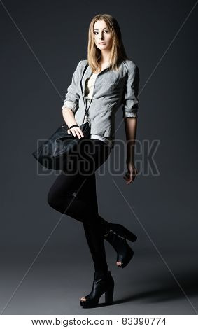 Studio Fashion Shot: Beautiful Young Woman In Leggings And Jacket, With Bag