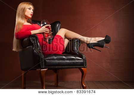 portrait of beautiful blonde lying in armchair with wine glass