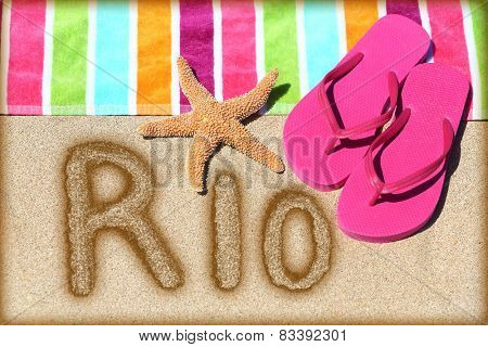 Rio beach concept. Overhead view ot the word RIO written on golden sand with a starfish, pink flip flops and towel conceptual of a summer vacation and travel in Rio de Janiero, Brazil