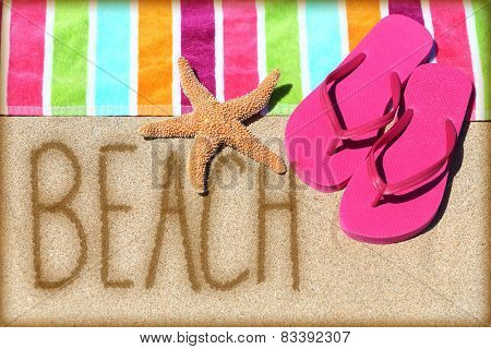Beach vacation concept - word written on golden sand with a starfish, pink flip flops and towel conceptual of a summer vacation and travel to a sunny destination for a relaxing suntan.