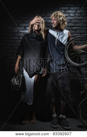 Attractive couple standing with bike on brick wall background