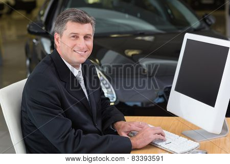 Smiling businessman typing on laptop at new car showroom