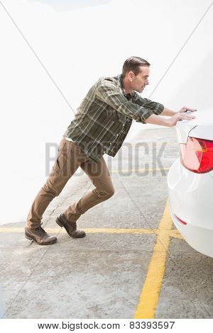 Man pushing his broken down car in a car park