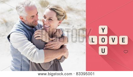 Happy hugging couple on the beach looking at each other against love you tiles