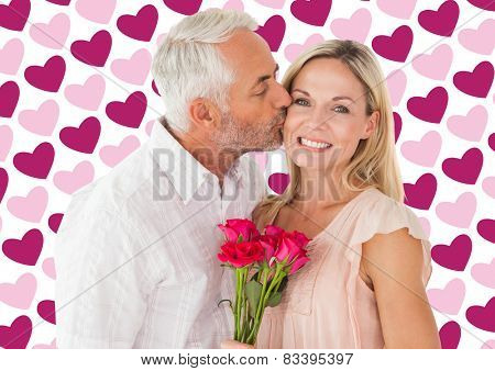 Affectionate man kissing his wife on the cheek with roses against valentines day pattern