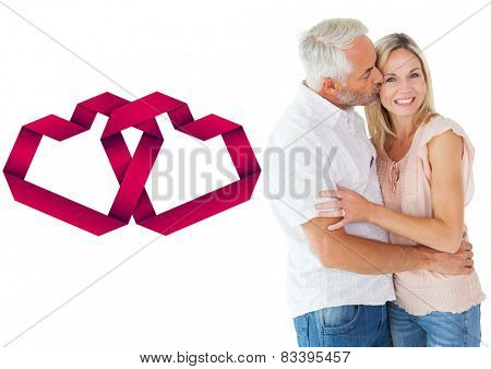 Affectionate man kissing his wife on the cheek against linking hearts