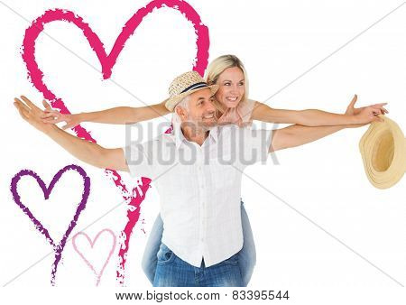 Happy man giving his partner a piggy back against valentines love hearts
