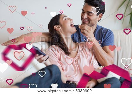 Playful couple watching TV while eating popcorn against love heart pattern